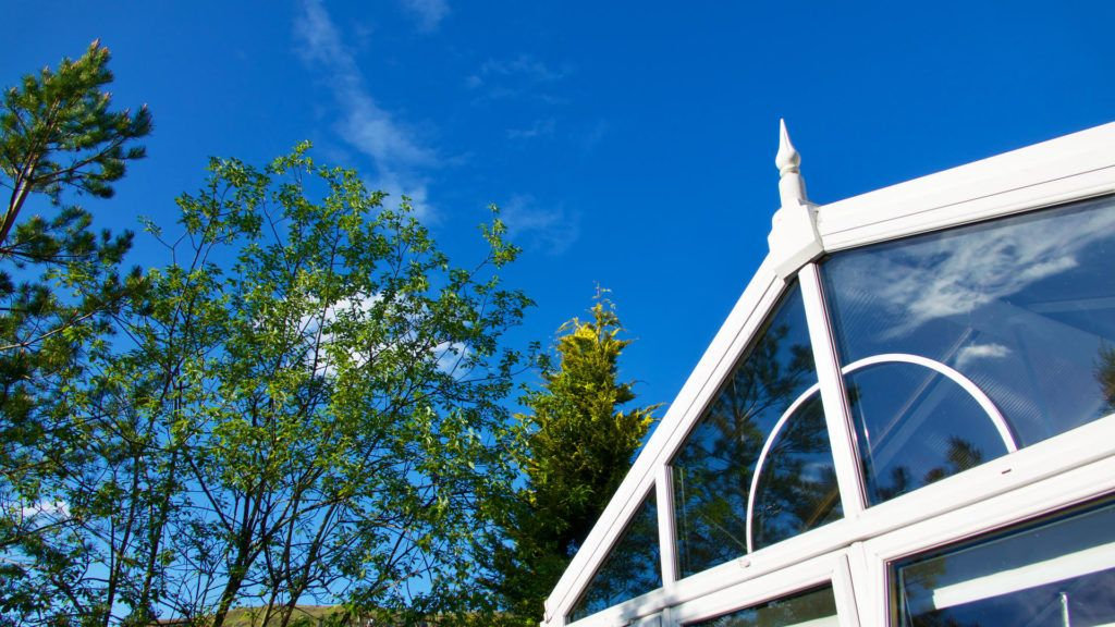 top of white upvc conservatory next to tree line