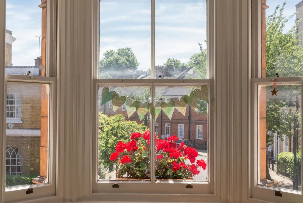 sash windows with bunting and red flowers in english town