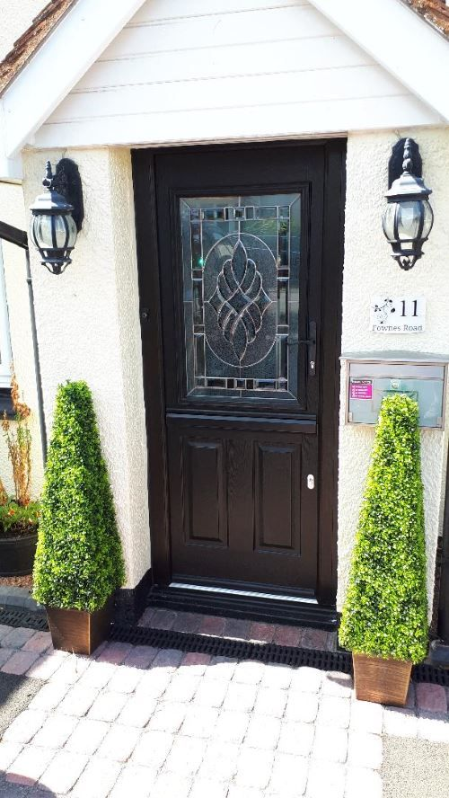 brown front door with hedge plants either side